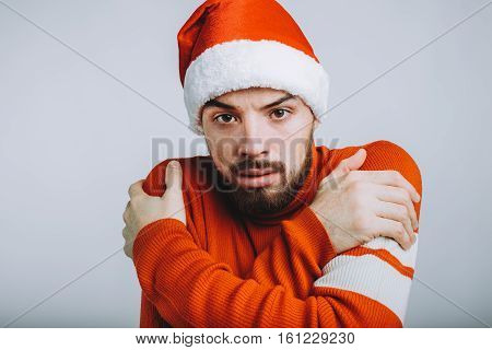 Handsome guy with beard hugging himself on white background. Serious man is looking at camera. He is wearing warm red sweater and santa claus hat