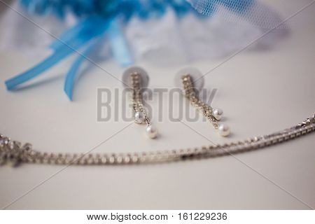 Garter of the bride women's earrings and chain lie on a white background wedding decorations are on the windowsill fees bride preparing for the wedding wedding jewelry close up
