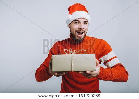 Handsome man holding a christmas gift. Happy man is wearing red warm sweater and Santa's hat. He is going to give this big present to his friends. Isolated on white background