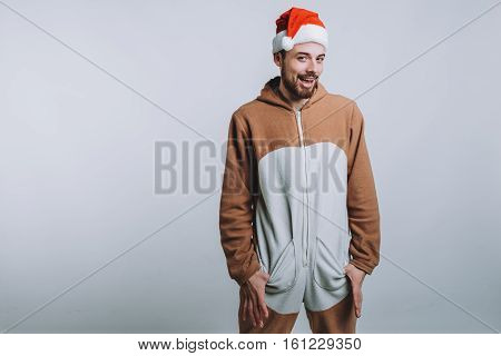 Young handsome man with noel or santa hat. Funny guy is wearing pajamas or fancy dress. Isolated on white background