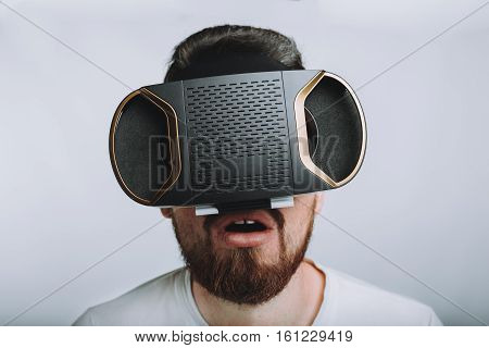 Young man trying vr goggles. Guy with beard in white shirt sees something astonished on its screen and he is amazed very much. Close up. Isolated on white background