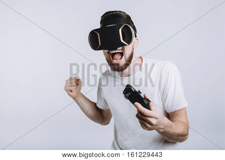 Young stylish guy trying vr goggles and holding joystick in his hand. He thinks he has won great fight or war that is why he is happy. Isolated on white background