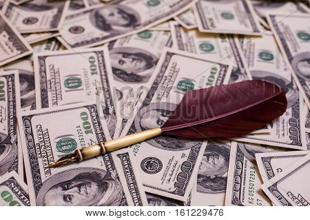 fountain pen lying on the background of hundred-dollar bills background of the money hundred dollar bills front side. background of dollars old hundred-dollar bill face