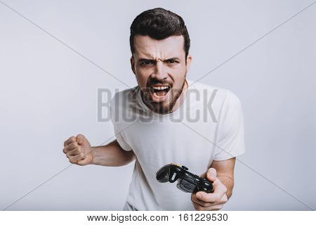 Young attractive guy with beard holding joystick. Serious man is screaming because of hardness and losing. He is angry and wants revanche. Isolated on white background