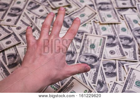 hand reaching for money background of the money hundred dollar bills front side. background of dollars old hundred-dollar bill face greed for money