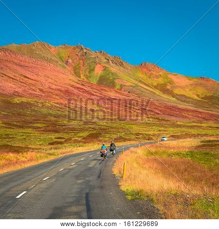 Lonely two travellers with bikes on Icelandic road summer time