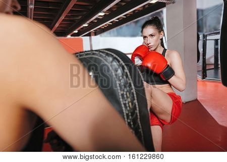 Hold it tight. Skillful pretty concentrated woman mastering her leg kick on a special pad while her friend helping her by holding it