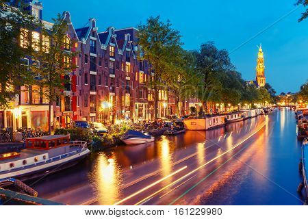 Night city view of Amsterdam canal Prinsengracht with houseboats and Westerkerk church and luminous track from the boat, Holland, Netherlands. Used toning