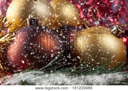Christmas balls lying on spruce branches. Blurred background and falling snowflakes