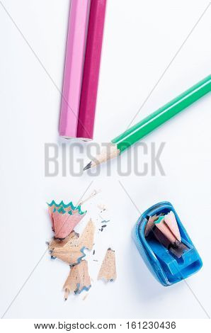 The open blue pencil sharpener and pencils lying on a white background not isolated