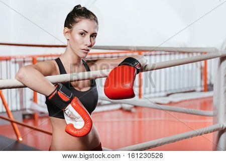 Do you want to test your skills. Beautiful serious young woman challenging you to fight her in the ring by looking straight at the camera