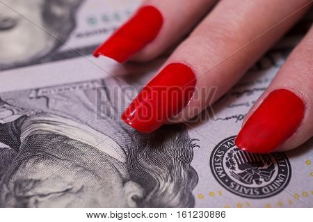 woman's hand with red nails lying on the money greed for money nails with red paint closeup background of the money hundred dollar bills front side. background of dollars new hundred-dollar bil face the evolution of the bill in one hundred dollars