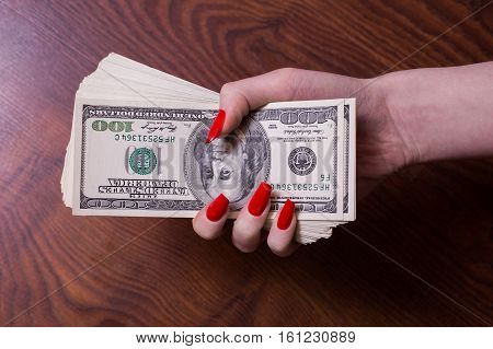 a bundle of money in a female hand with red nails greed for money hundred dollar bills front side old hundred-dollar bil face
