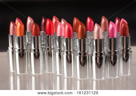 Tubes with different kinds of lipstick on studio background
