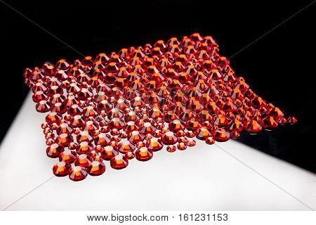 Red crystals on a glass studio background