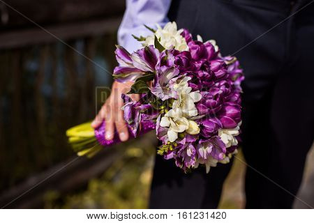bunch of white and purple flowers in hand groom bouquet of flowers in a man's hand a businessman holding a bouquet of flowers