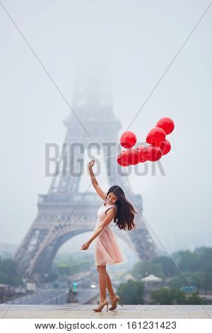 Parisian Woman With Red Balloons In Front Of The Eiffel Tower