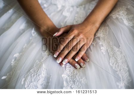 female hands on the wedding dress the bride morning preparing for the wedding white nails manicures