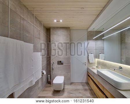 Bathroom in a modern style with textured tiles and a wooden ceiling. There is a white sink on the rack, wooden lockers, mirror, towel holders, toilet, shower, door, wooden panel above the sink, lamps.