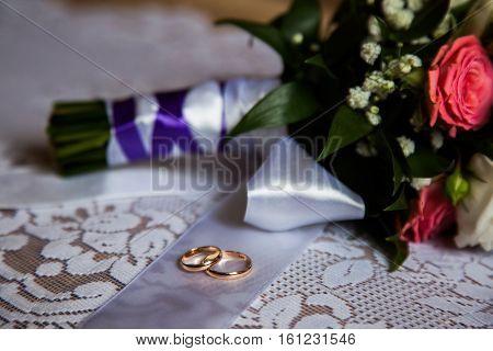 wedding rings lie on a ribbon bridal bouquet wedding preparation wedding decorations