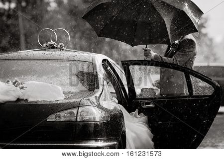 the groom sees the bride in the car, rain during the wedding, black and white wedding photography, wedding photography conceptual groom holding an umbrella, wedding gown