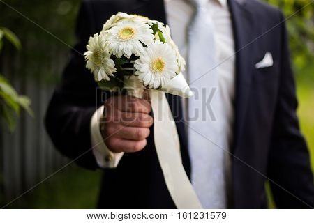 groom holding a bouquet of white daisies bouquet of white flowers in male hands