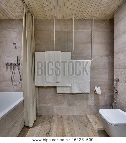 Modern bathroom with textured tiles and a wooden ceiling. There is a white bath with a curtain and a shower, towel holders, toilet with another shower, toilet paper holder. Horizontal.