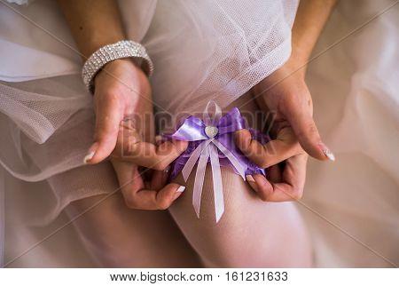 purple blue garter on leg of the bride morning bride the bride wears a garter on the leg the preparations for the wedding