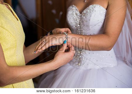Girl wears a bracelet on a hand of the bride bride's morning preparing for the wedding the bride's fees dress decorate the bride wedding attributes jewelery bracelet bride dress