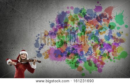 Attractive young woman in Santa suit playing violin