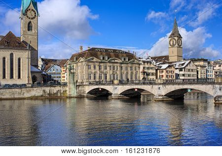 Zurich, Switzerland - 1 February, 2015: the Munsterbrucke bridge over the Limmat river, clock towers of the Fraumunster and Saint Peter church, old town buildings in the background. Zurich is the largest city in Switzerland.