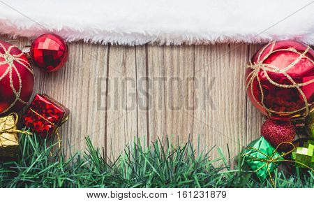 Santa Claus hat on Wooden with Balls and Gift Boxes with Green Grass in Vintage Tone