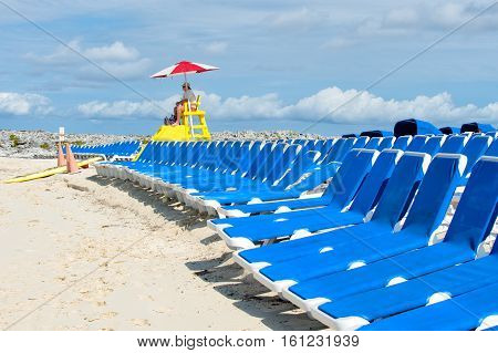 Great Stirrup Cay Bahamas - January 8 2016: lifeguard or beach rescue man on duty sits on tower chair and supervises safety of people in water during sea vacation and empty sunbed on blue sky