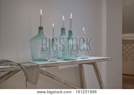 Burning candles in the stylish bottles on the wooden table on the white wall background. There is a shawl near them. Behind the bottles there are power sockets on the wall. Closeup. Horizontal.
