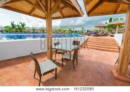 Cayo Guillermo island, Iberostar Playa Pilar hotel, Cuba, June 28, 2016, nice beautiful inviting view of comfortable swimming pool and bar sitting area with people relaxing, swimming in background