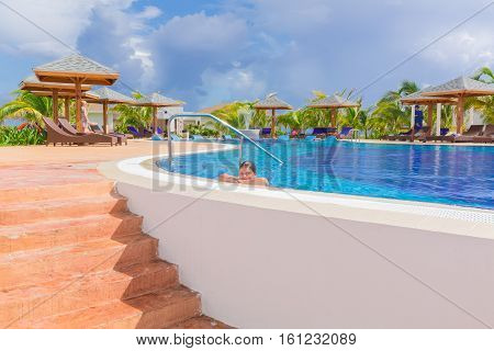 Cayo Guillermo island, Iberostar Playa Pilar hotel, Cuba, June 28, 2016, beautiful inviting view of comfortable cozy swimming pool with smiled little girl relaxing swimming and enjoying her vacation