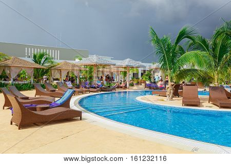 Cayo Guillermo island, Iberostar Playa Pilar hotel, Cuba, June 28, 2016, nice beautiful inviting view of a curved comfortable swimming pool with sun beds on blueish gray sky background