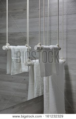 Hanging white wooden towel holders with white towels on the mirror background in the modern bathroom with gray wooden walls. Closeup. Vertical.
