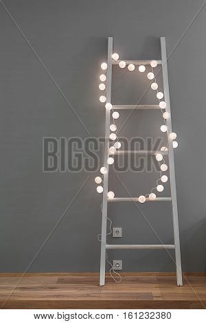 White ladder with glowing sphere lamps in a form of the garland on the gray wall background. There is a parquet on the floor and power sockets on the wall. Closeup. Vertical.