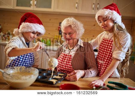 kids baking cookies with grandmother on xmas time