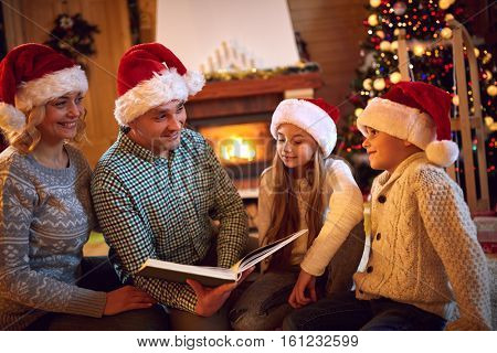 Christmas eve - happy family time. Smiling family read book