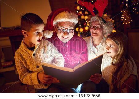 concept of Merry Christmas- family reading magic book
