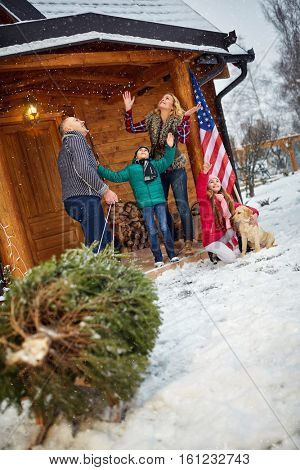 smiling family with Christmas tree on snowy day enjoying