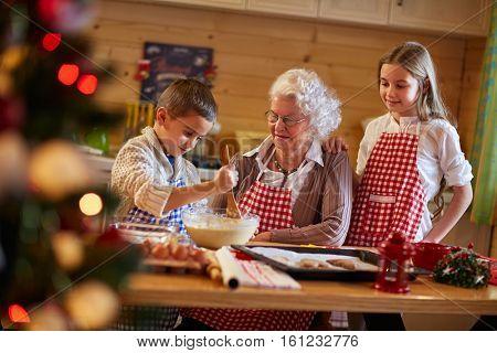 grandmother helping grandchildren preparing Christmas cookies- holiday season
