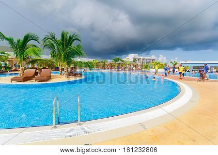 Cayo Guillermo island, Iberostar Playa Pilar hotel, Cuba, June 28, 2016, beautiful inviting view of a curved wide open comfortable swimming pool with entertainment team and people enjoying their time on sunny gorgeous day