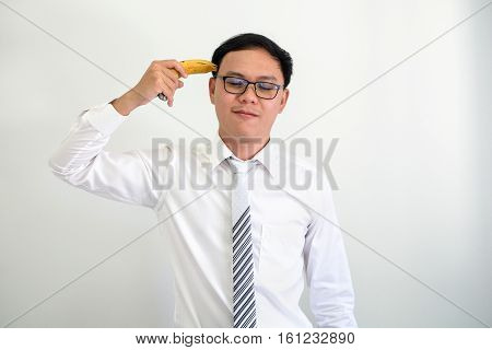 portrait of young ceo bussinessman points a banana at his head.