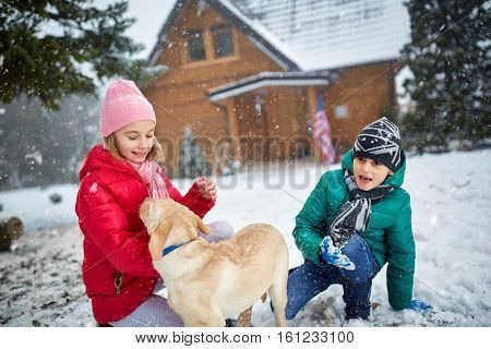 smiling children with dog playing on snow in winter holiday