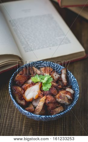 deep fried pork and the book on wooden in vintage tone