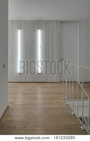 Contemporary corridor with white walls and a parquet on the floor. There are glowing tube lamps on the wooden wall, door, white stair with metal railing, switch. Vertical.