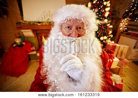 Real Santa Claus gesturing shhh with finger on mouth